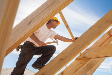 roofer builder working on roog structure of building on construction site