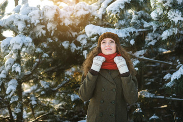Pretty young woman in hat and coat play in snow winter park