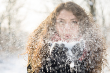 Woman blows on snow in her hands