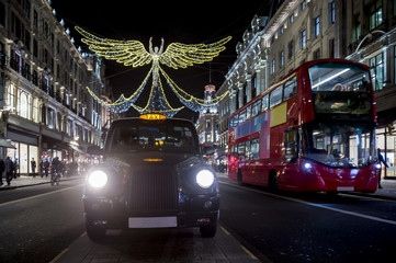 Red double-decker bus and black cabpass under twinkling Christmas lights along the upscale shopping district of Regent Street.