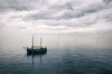 Old traditional fishing boat returning to port under dramatic cloudy skies.