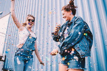 Young adult best friends cheering with confetti on party
