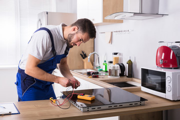 Technician Repairing Induction Stove In Kitchen