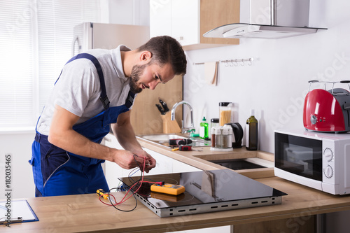 technician repairing induction stove in kitchen stock photo and royalty free images on fotolia. Black Bedroom Furniture Sets. Home Design Ideas