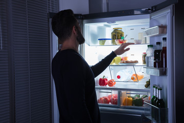 Man Looking At Food Kept In Refrigerator
