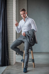 Elegant young man in tuxedo sitting on a stool