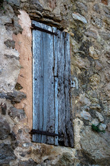 Closed Old External Timber Window Shutter in Rustic Stone Wall Spain