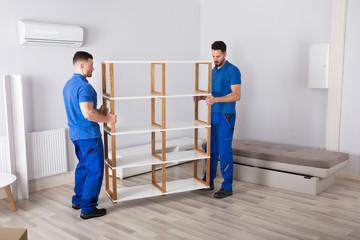 Two Men Holding Shelf In Living Room