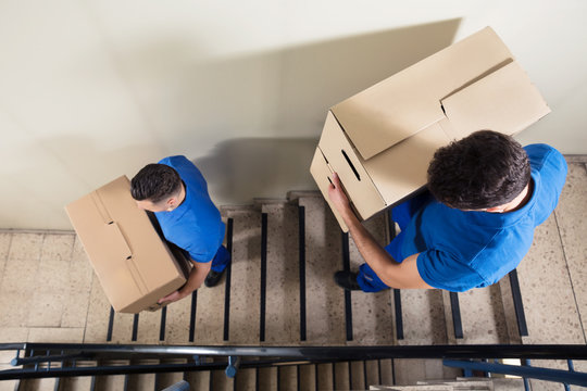 Two Movers Carrying Cardboard Boxes On Staircase
