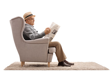 Mature man sitting in an armchair and reading a newspaper