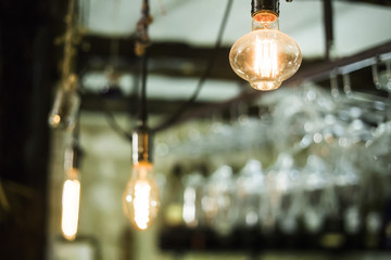 Decorative light bulbs with yellow light hang over the bar in front of the glasses