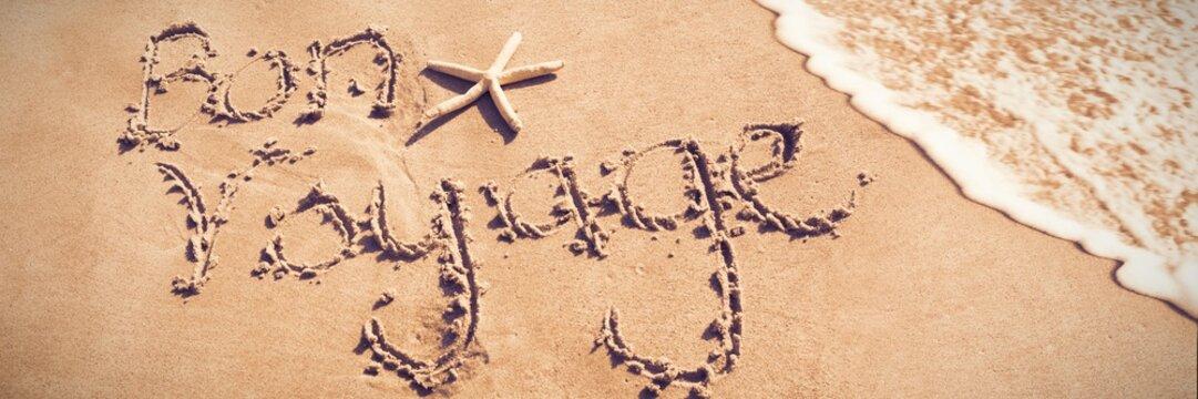 Bon voyage written on sand