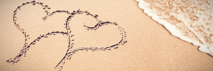 Two heart shapes inscribe on sand