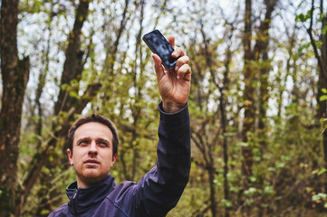 Man with his mobile smart phone searching for reception signal in the forest.