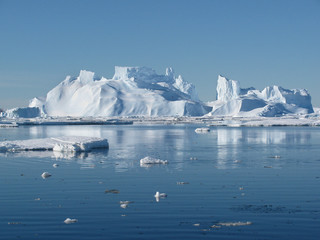 Iceberg floats on open water. You can see the underwater part of it and the ice floes near it. Antarctic.