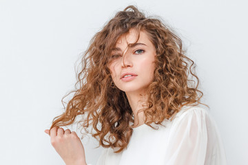 Ginger girl with shiny curly and wavy hair in hairdresser salon