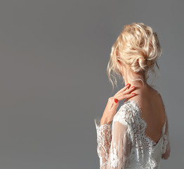 Rear view portrait of attractive young woman with beautiful wedding hairstyle and dress