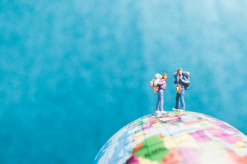 Miniature Backpacker , Travelers with backpack standing on world map and walking to destination