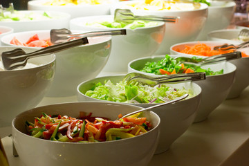 Salad bar. Fresh vegetables in white bowls
