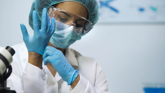 Biracial girl putting latex gloves on at laboratory, preparing for research
