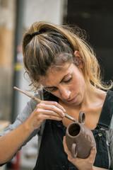 Confident woman creating clay pot