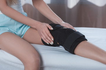 woman sitting at clinic with knee brace