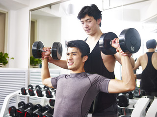 asian young adult working out in gym using dumbbells getting helped from trainer