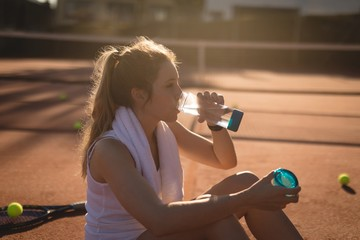 Tennis player drinking water after workout