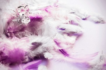 Small glass angel on pink and violet feather background.