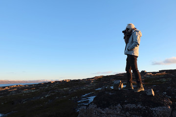 Woman traveler took a photo with beautiful landscape of tundra meadow
