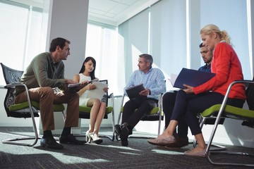 Business colleagues discussing while sitting at office