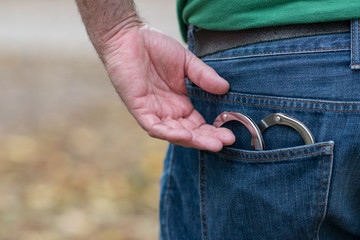 Metal handcuffs in back jeans pocket