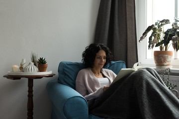 Beautiful woman relaxing on sofa and reading book