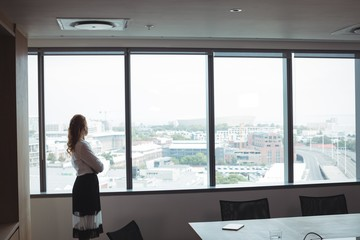 Side view of businesswoman looking out through glass window at