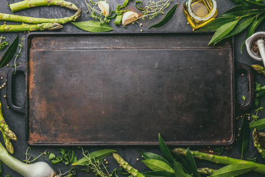 Food background with free space for text. Herbs, olive oil, spices around cast iron frying board. Top view