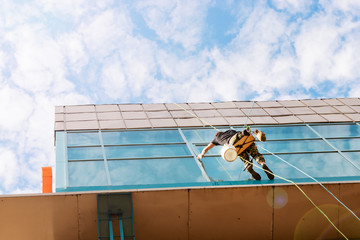 Industrial climber hanging on the clothesline and washes Windows, glass facade modern building