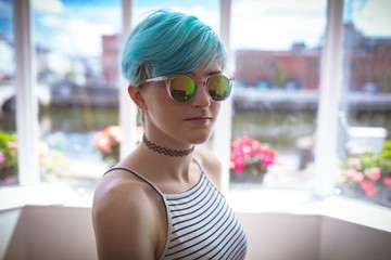 Woman in sunglasses posing at home