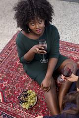 Junge dunkelhäutige Frau trinkt Wein