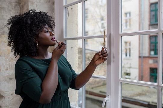 Dunkelhäutige Frau schminkt sich am Fenster