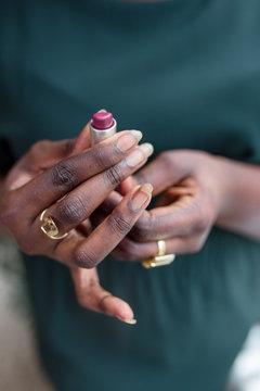 Dunkelhäutige Frau hält Lippenstift