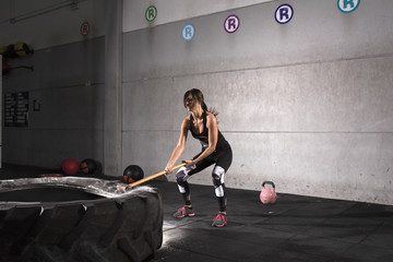 Sport Fitness woman Hitting Wheel Tire With Hammer Sledge crossfit training.