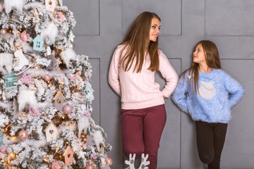 Young mother and her ittle daughters opening a magical Christmas gift by a Christmas tree in cozy living room in winter