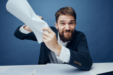 Business man with a beard working with documents on a blue background