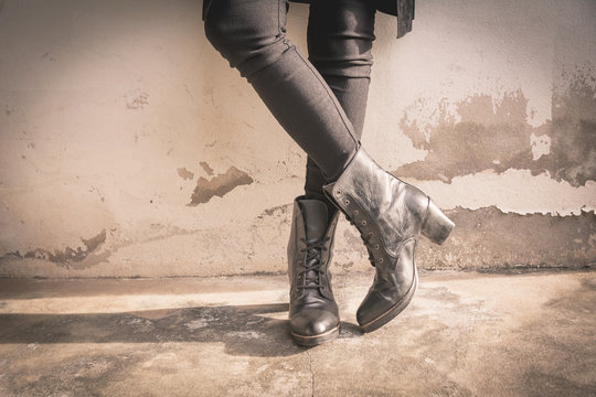 A woman legs wearing black boots with high heel. Sepia tone.