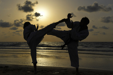 Karate fighters at sunset on the beach