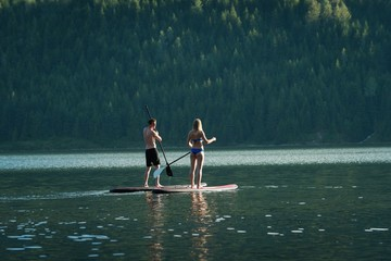 Couple doing stand up paddleboarding in river