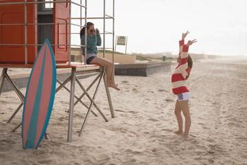 Teenage girl taking photo of her friend in beach