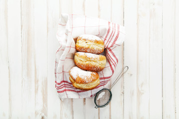Set of three sufganiyot doughnuts with jelly arranged in a box on white wooden background. Horizontal composition.