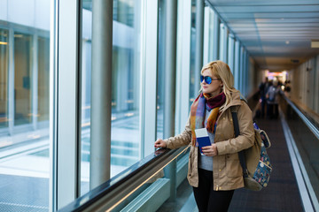 Young woman traveler in international airport with backpack holding passport in her hand