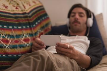 Man in headphones using mobile phone